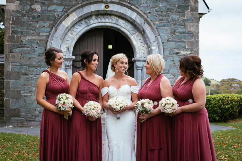 bride and her bridesmaids outside bride and groom embracing at Gougane Barra church