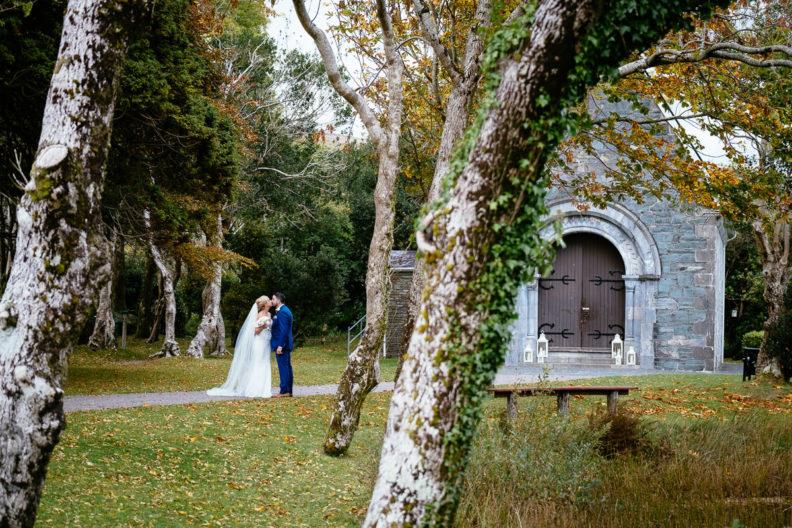 bride and groom kissing outside Gougane Barra church