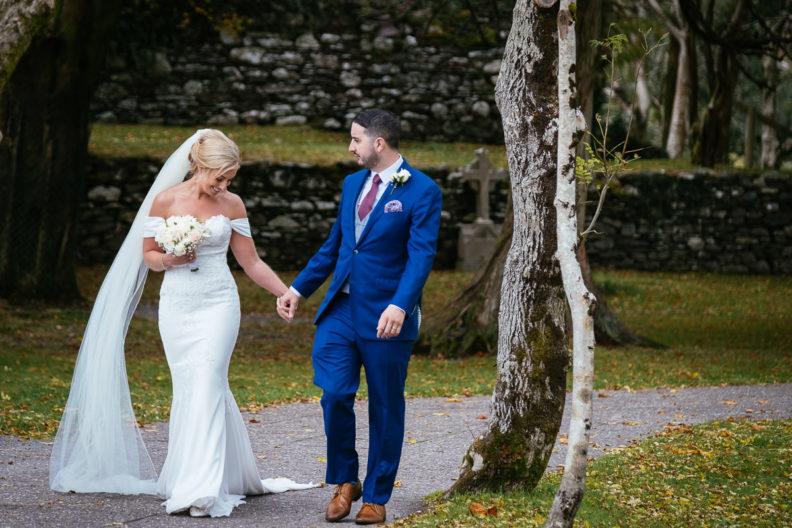 bride and groom walking outside Gougane Barra church