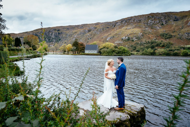 bride and groom standing by the lake outside Gougane Barra church