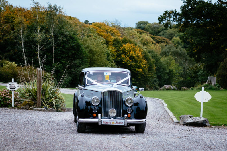 bride and groom arriving in wedding car at ballinacurra house