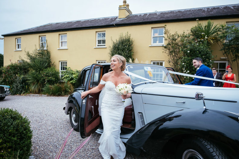 bride getting out of wedding car at ballinacurra house