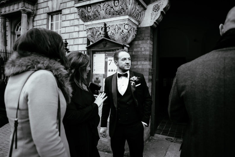 groom looking pensive outside church