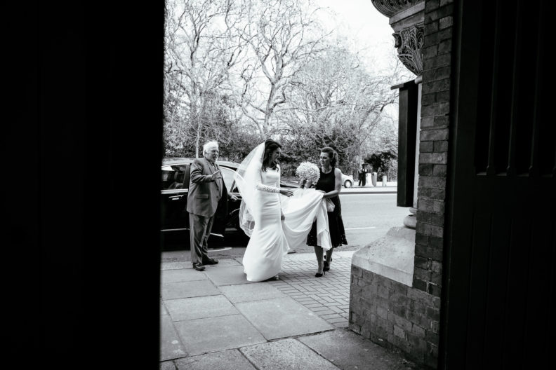 bride fixing her dress outside church door