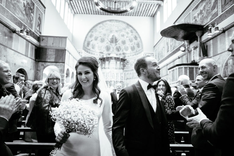 bride and groom leaving church laughing