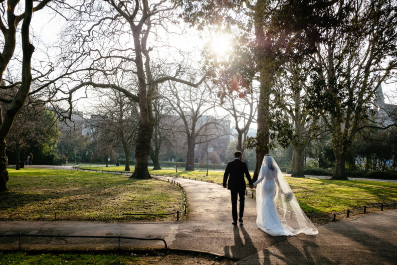 bride and groom walking through st stephens green into sunset holding hands