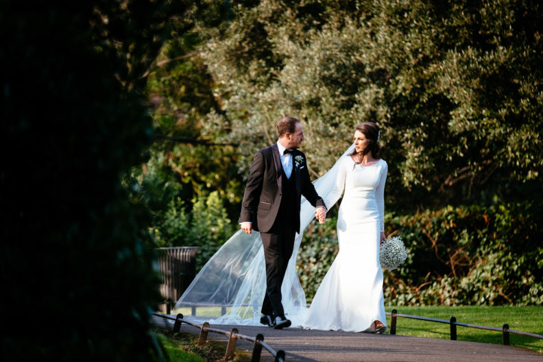 bride and groom walking through a park