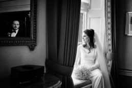 Bride sitting by a window with her grooms reflection in a mirror