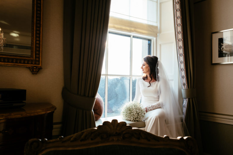 bride sitting by a window bathed in sunlight