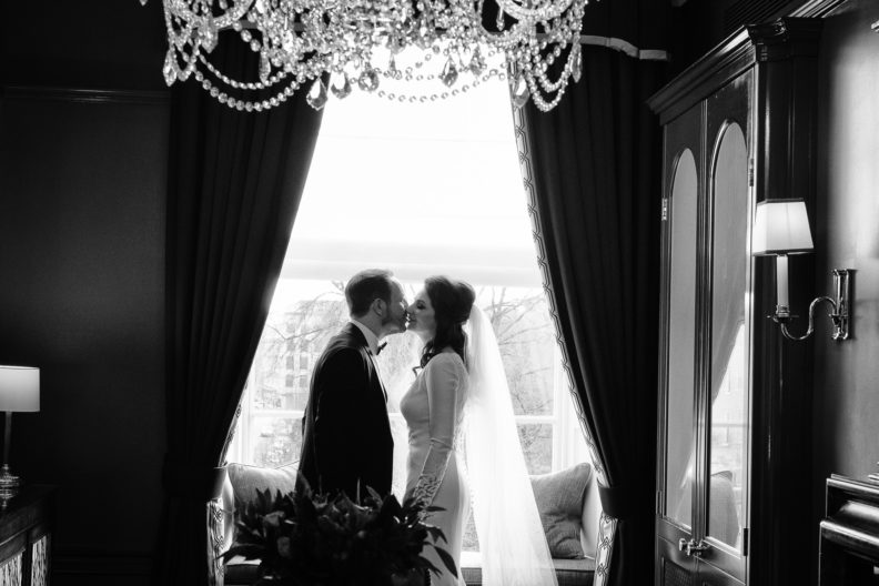 bride and groom kissing by a large window