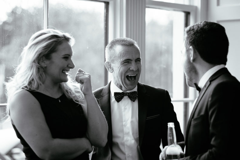 male wedding guest laughing