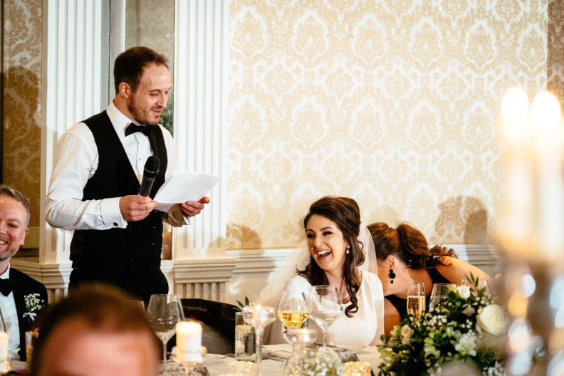 groom making a speech with bride laughing
