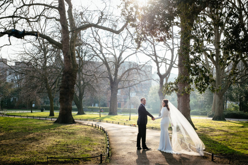 bride and groom walking through st stephens green into sunset