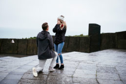 guy on one knee proposing to his girlfriend at the cliffs of moher