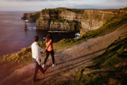 engaged couple walking along a cliff edge at sunset