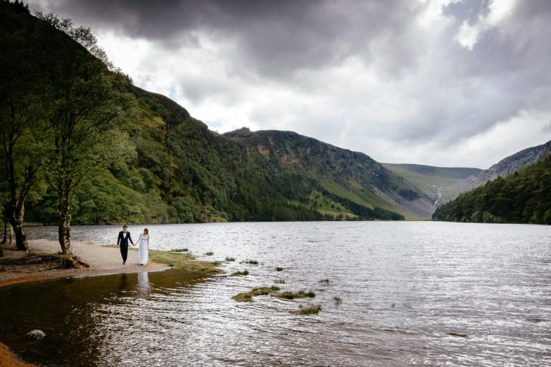 engaged couple walking along by a lake in ireland