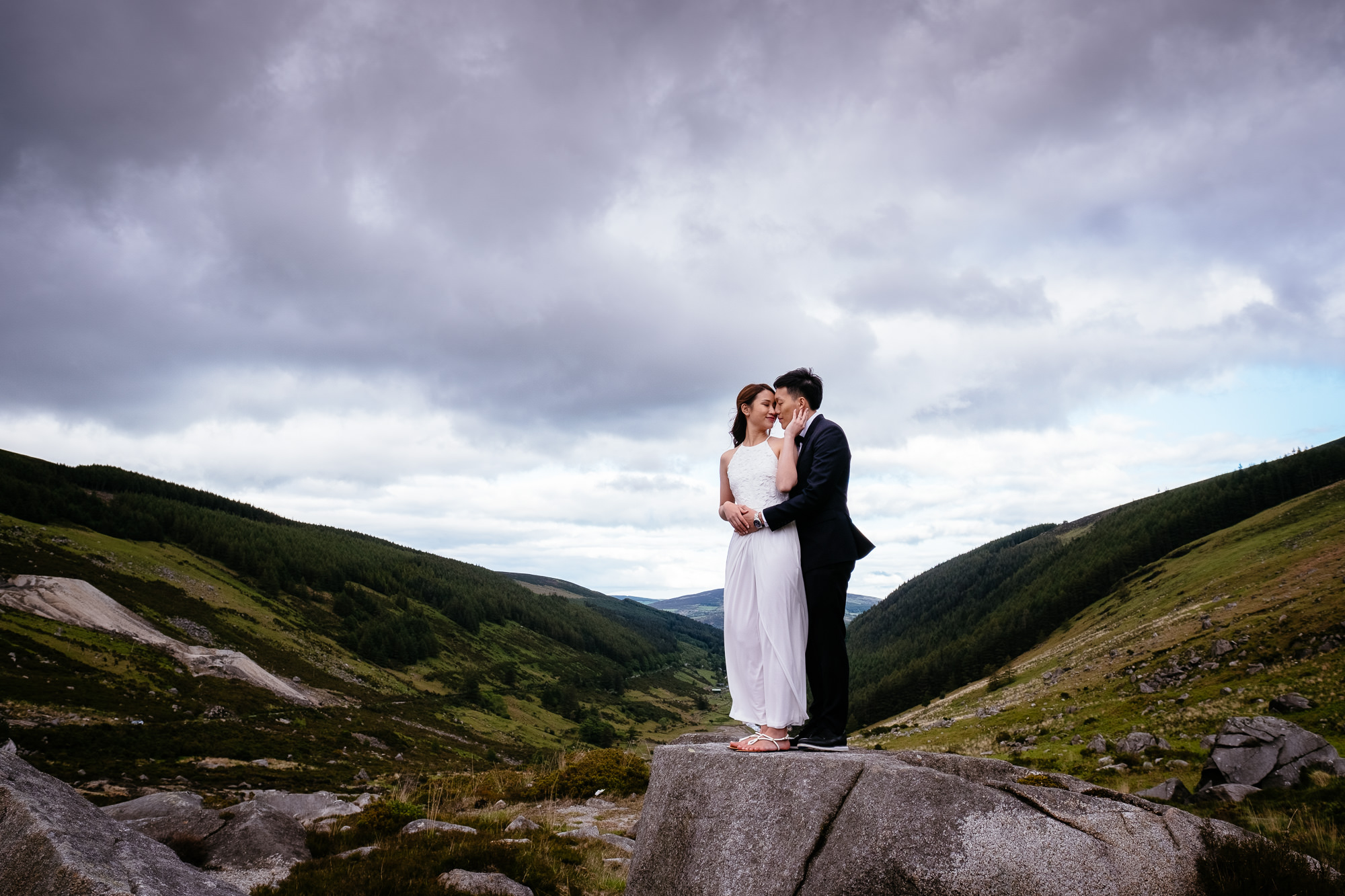 engaged couple standing in a valley in ireland