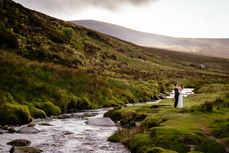 engaged couple walking along by a river in ireland
