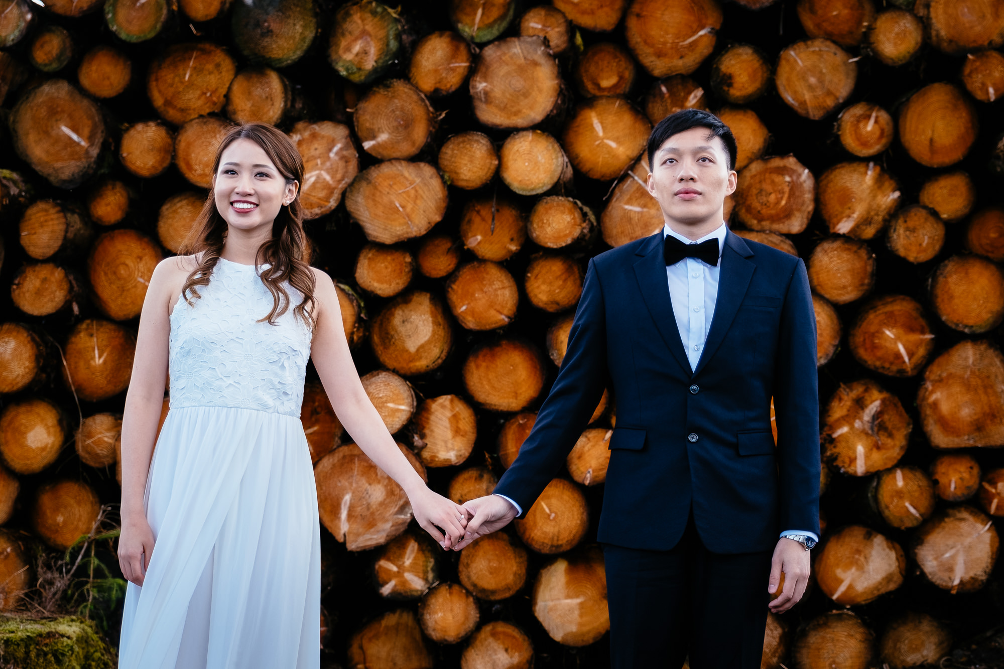asian couple holding hands by cut timber in rural Ireland