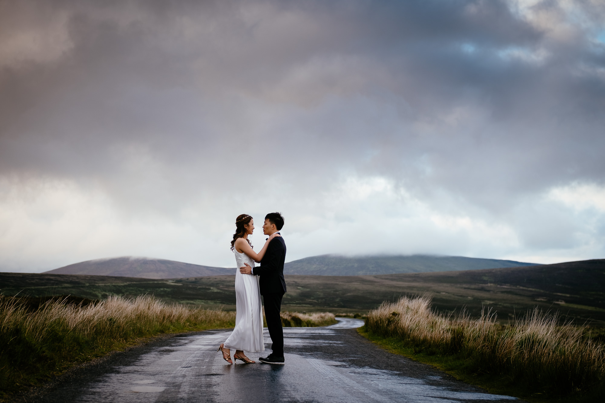 engaged couple hugging on a deserted road in irish mountains