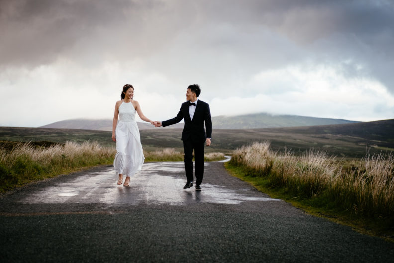 engaged couple walking along a deserted road in irish mountains