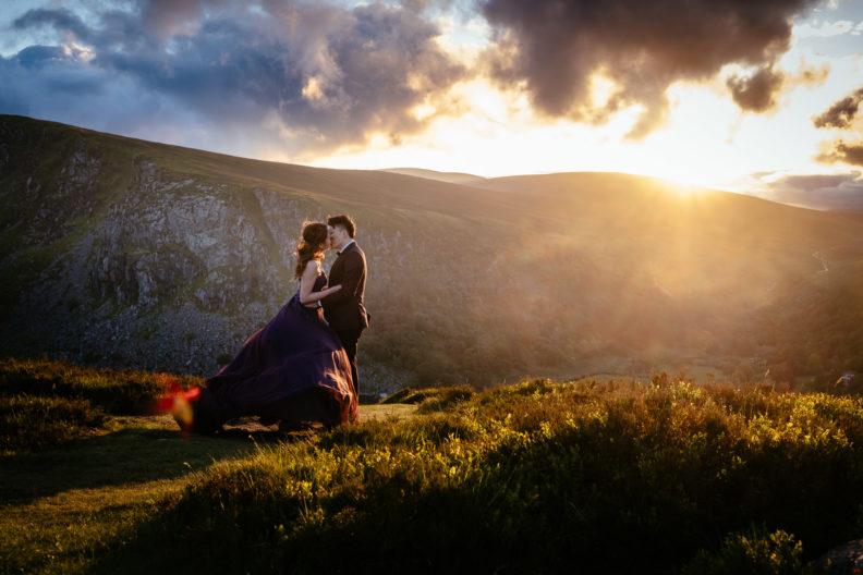 engaged couple hugging at sunset in irish mountains
