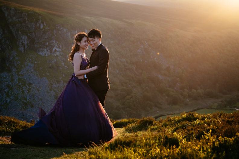 engaged couple embracing at sunset in irish mountains