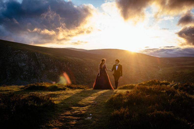 engaged couple walking at sunset in irish mountains