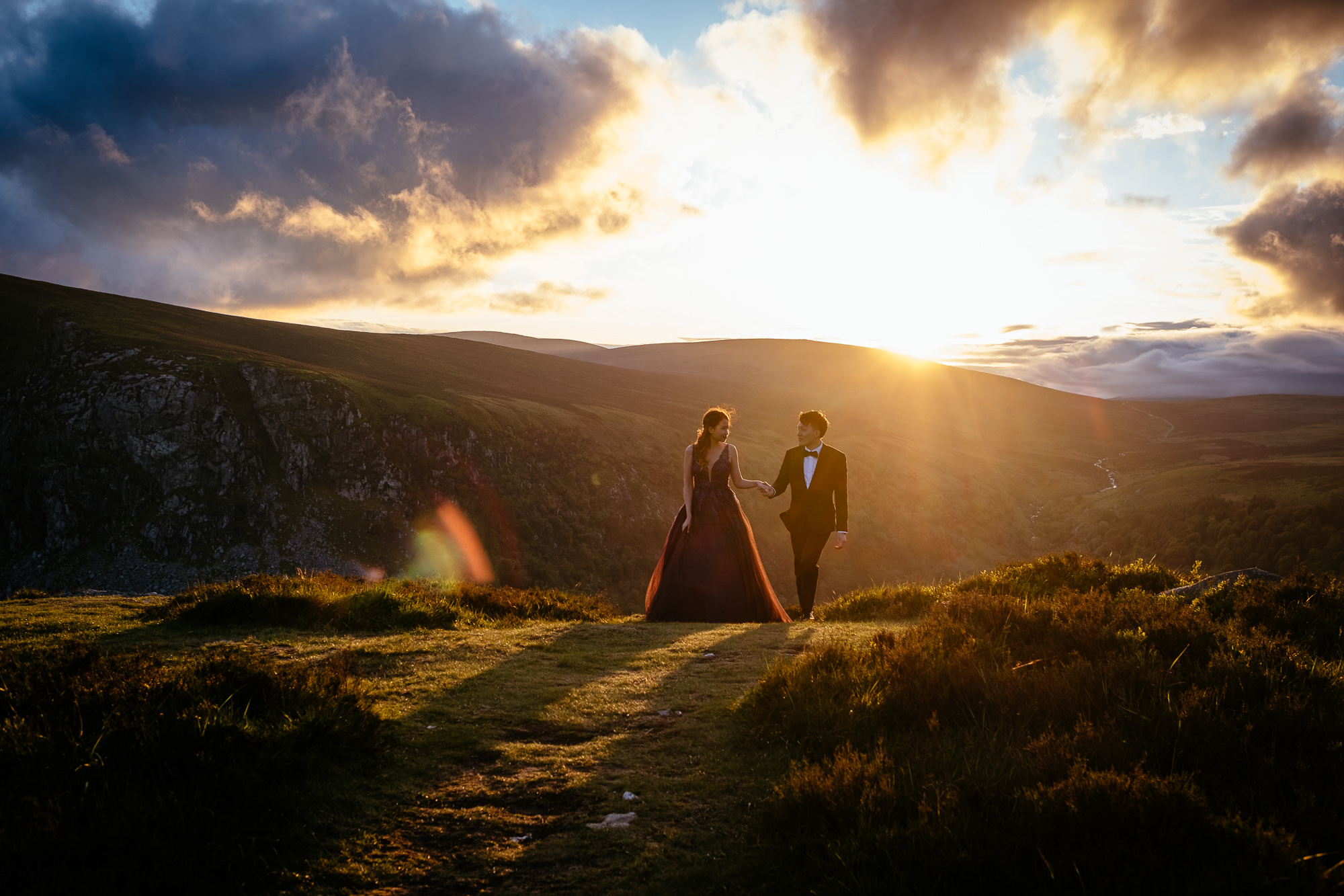 engaged couple walking at sunset in irish mountains