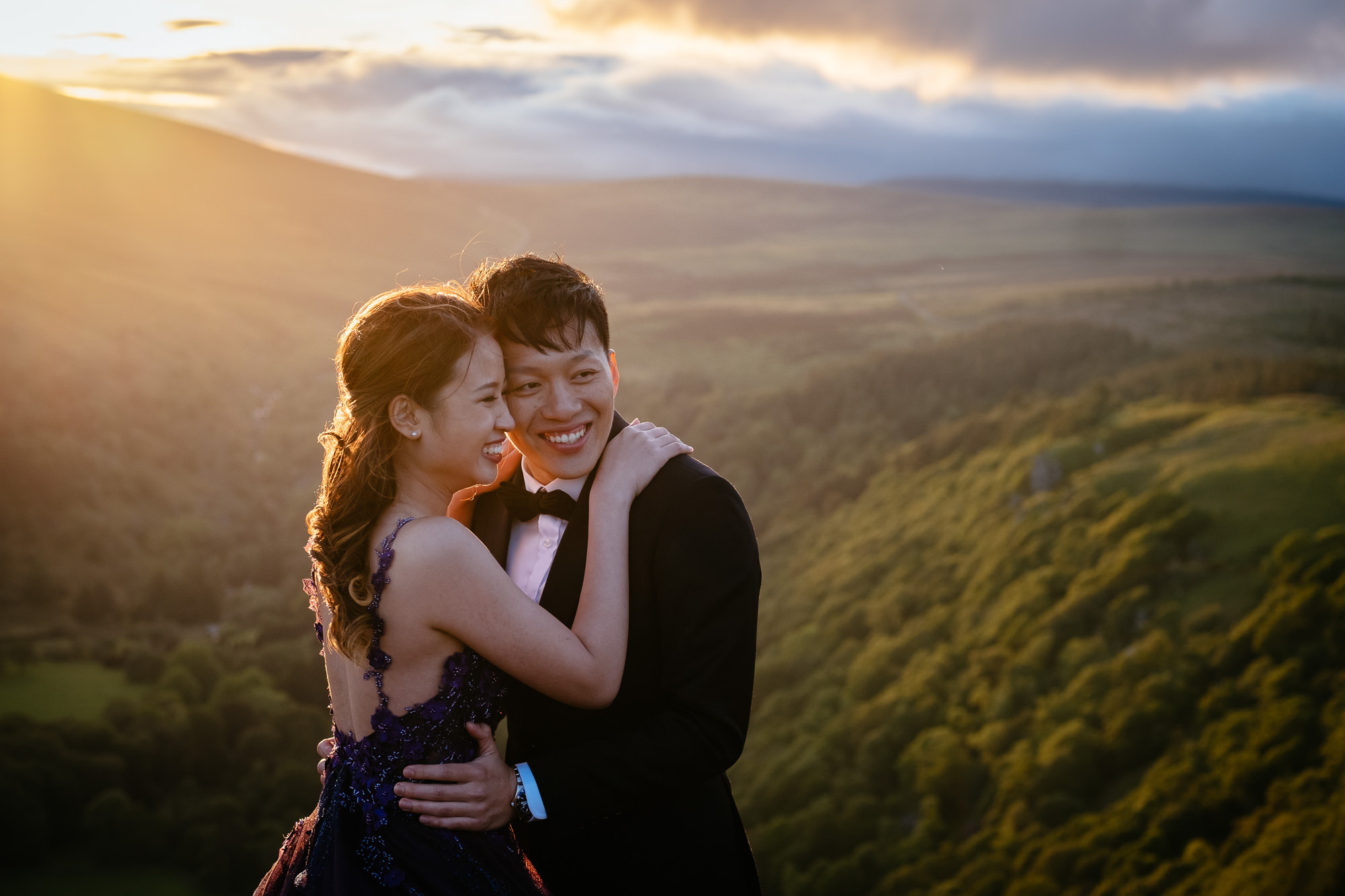 engaged couple hugging and laughing at sunset in irish mountains