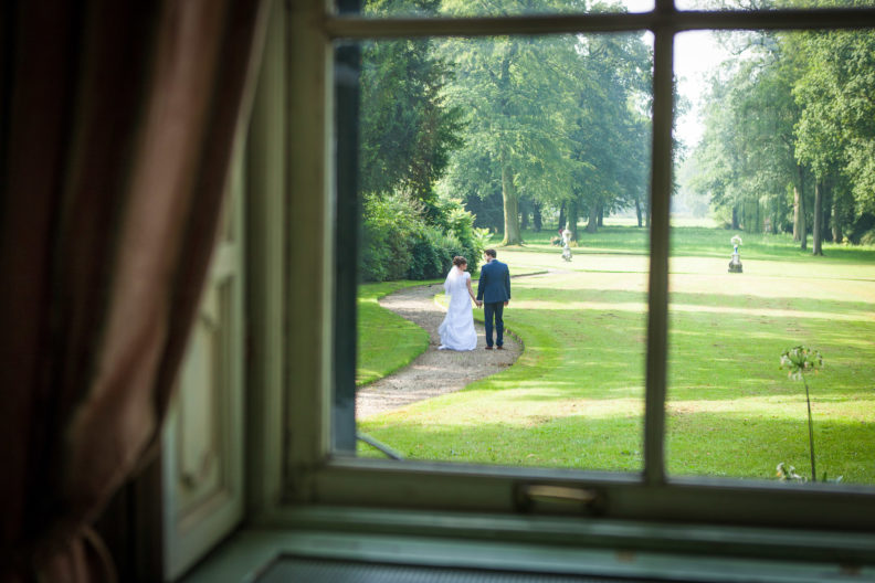 bride and groom viewed through a window walking in a large garden