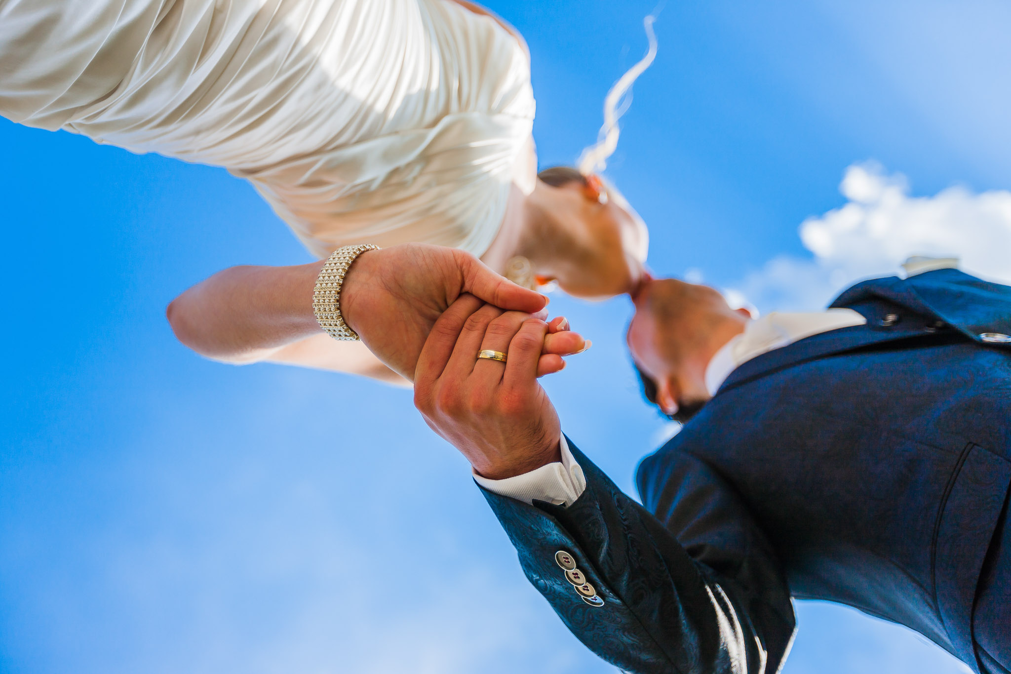 bride and groom holding hands kissing against a blue sky