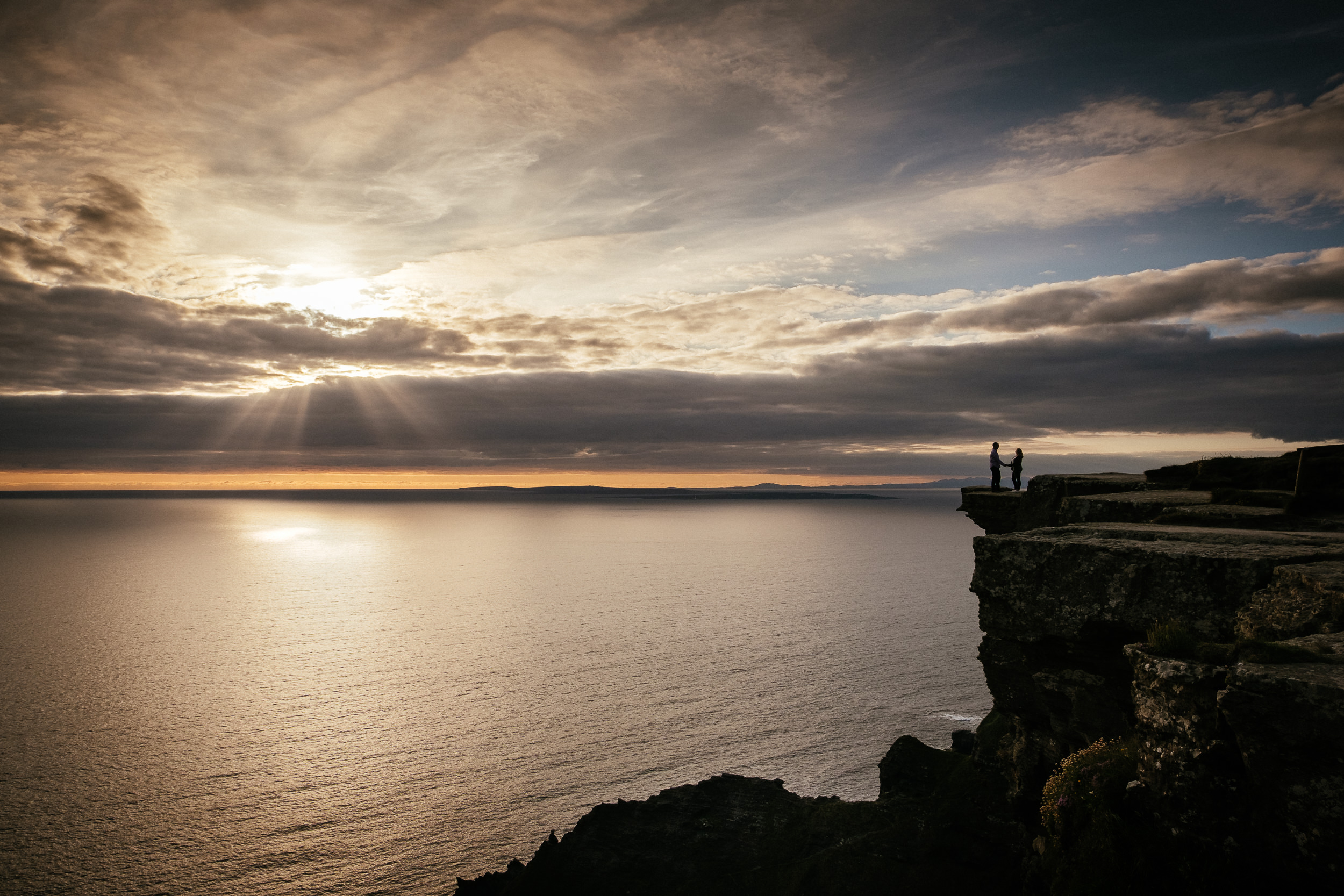 bride and groom standing on the cliffs of moher with the sun setting behind them