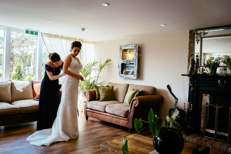 bride being helped into her dress at ballymagarvey village