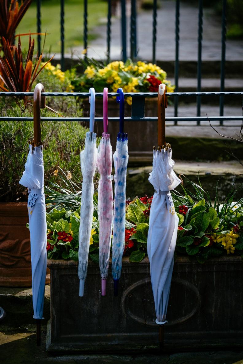 umbrellas hanging on a railing