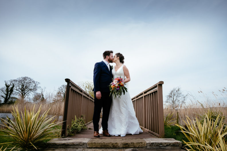 bride and groom standing on a jetty kissing