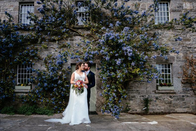 bride and groom embracing in front of doorway