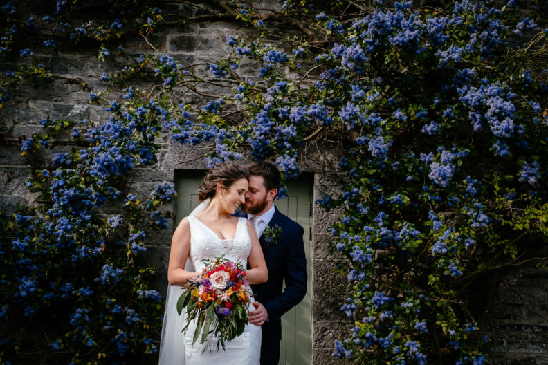 bride and groom embracing in front of doorway with purple flowers