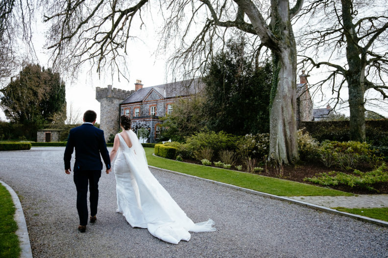 bride and groom walking towards a house
