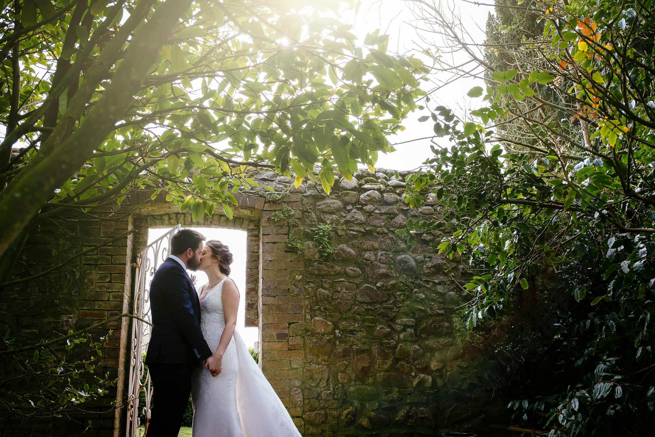 bride and groom embracing in front of doorway with sun setting behind