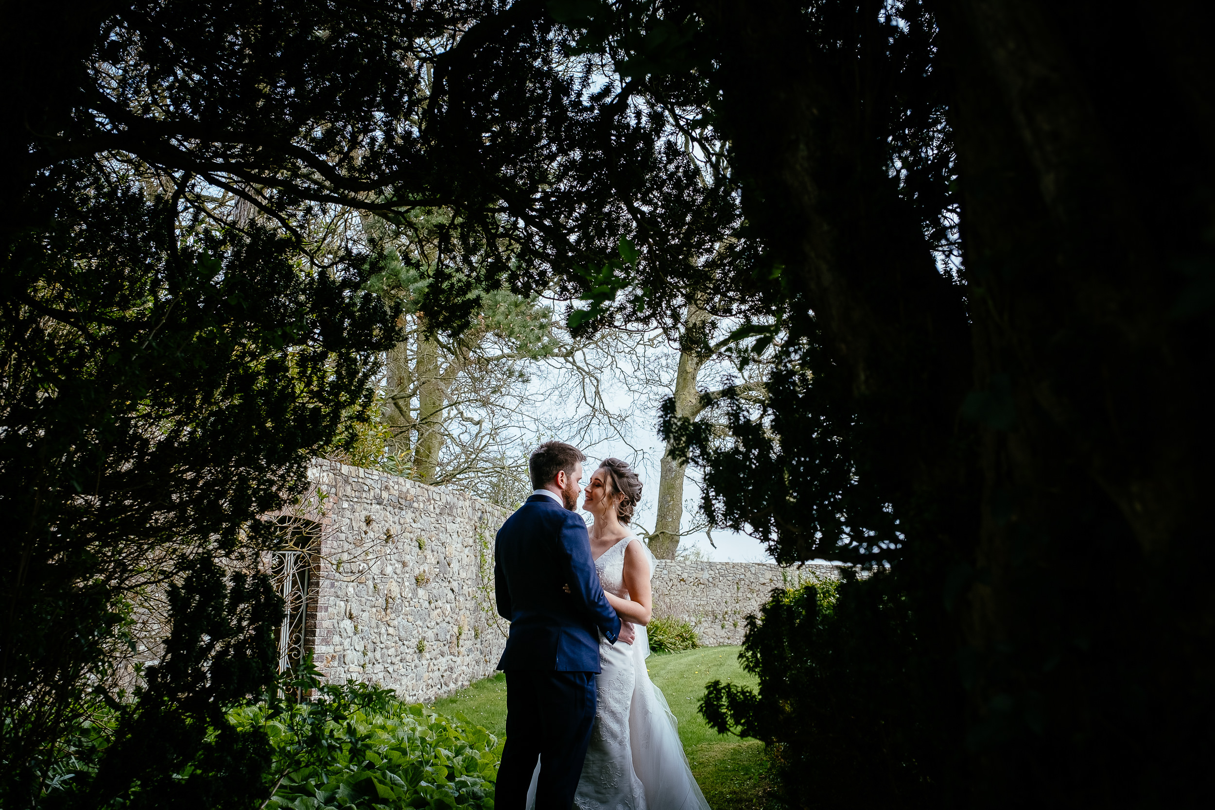 bride and groom kissing through a gap in trees at Ballymagarvey village meath