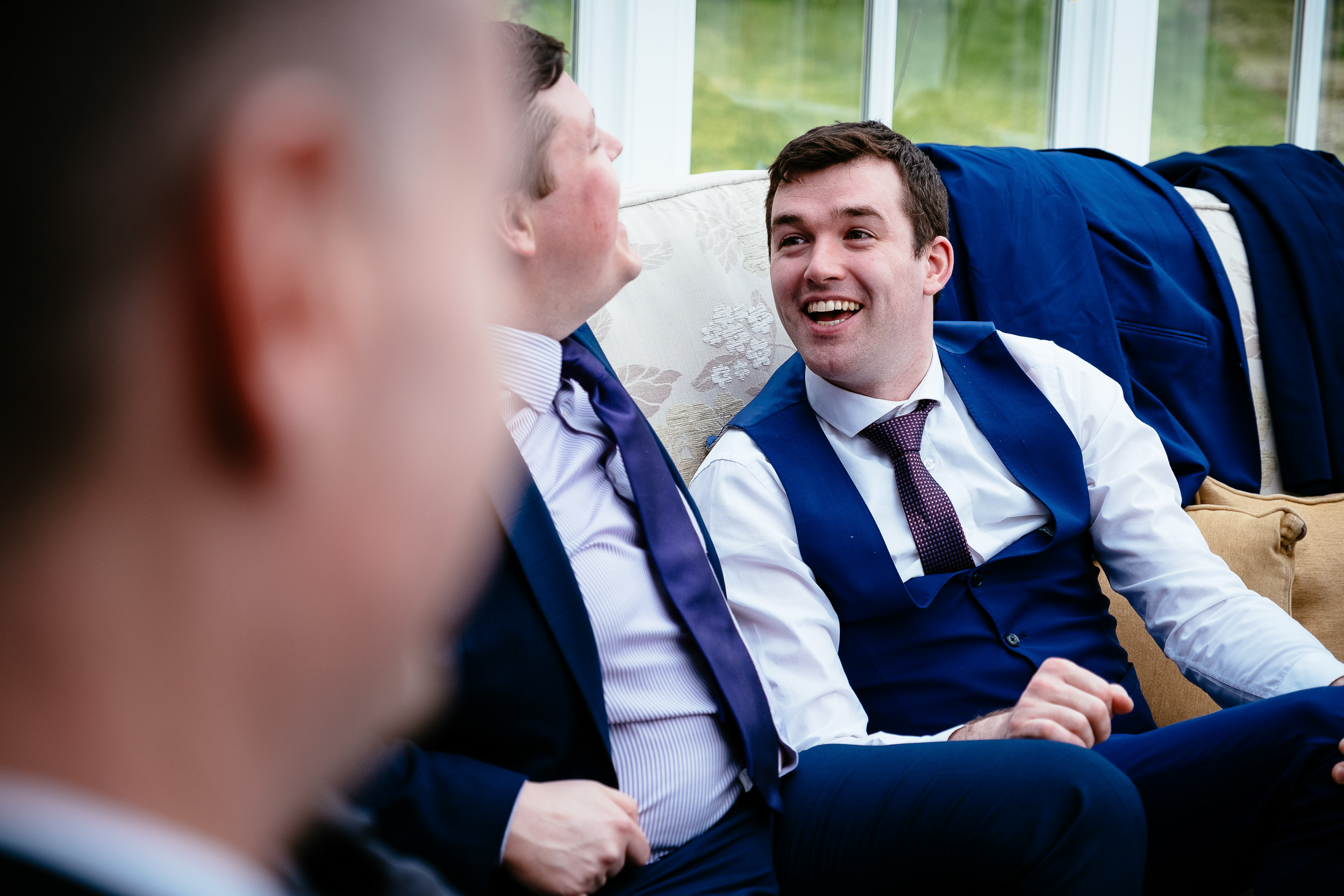 two male wedding guests laughing