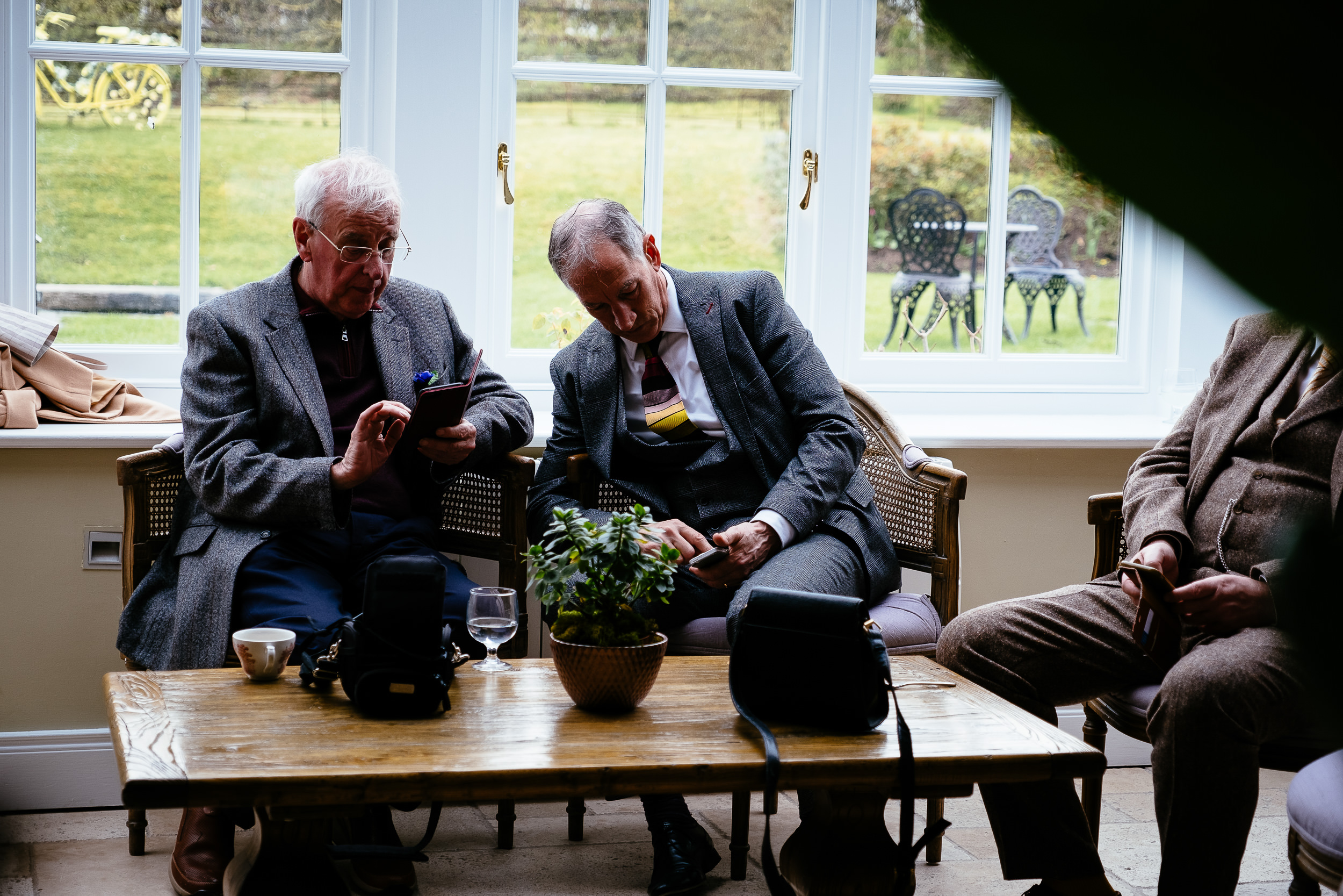 two old men checking their mobile phones