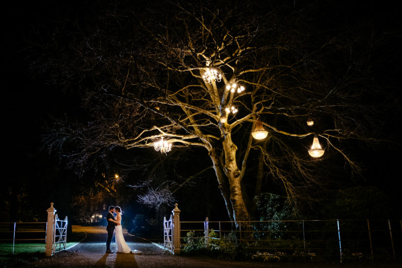 bride and groom embracing under a tree with lanterns at night in ballymagarvey village