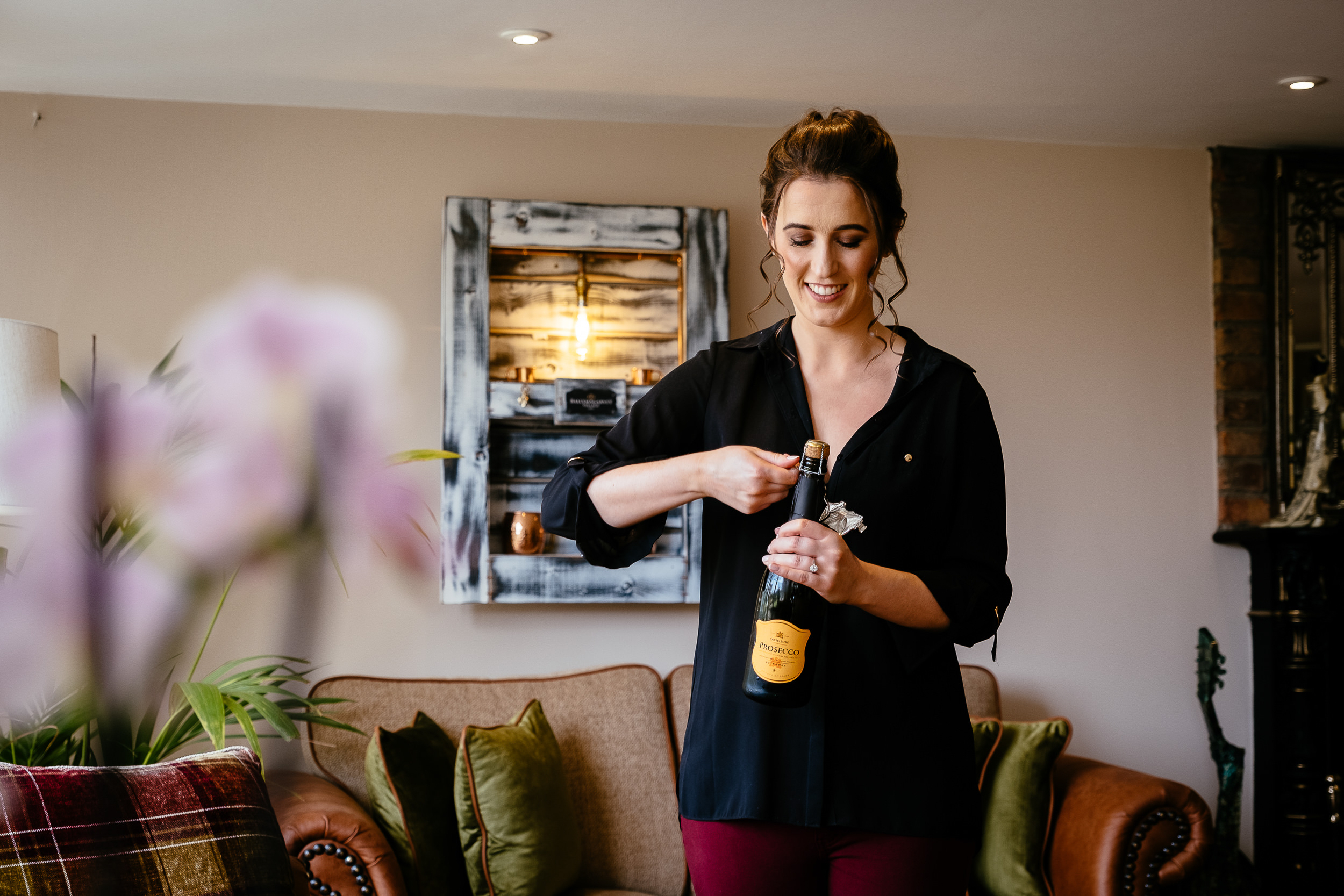 bride opening a bottle of champagne at Ballymagarvey village meath