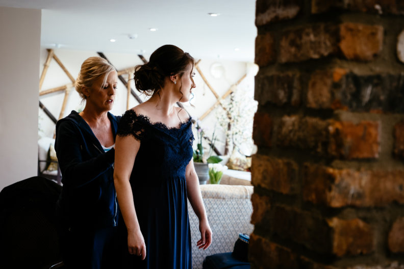 bridesmaid having her dress buttoned up