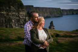 engaged couple hugging at cliffs of moher