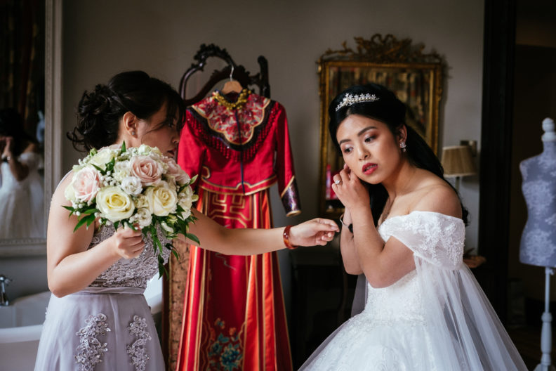 bride putting on ear ring