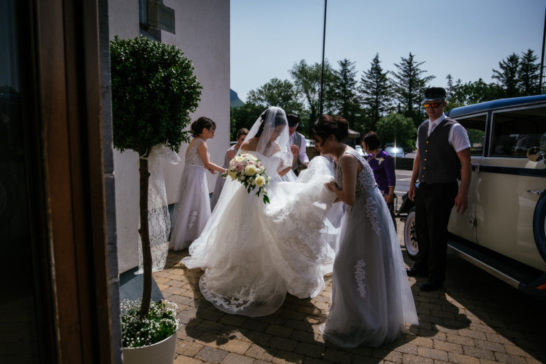 bride being helped by bridesmaids outside church