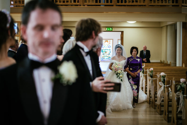 bride walking up aisle with mother